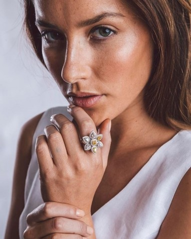 model wearing engagement or dress ring that looks like a flower with the petals and centre made of pastel coloured diamonds surrounded in white diamonds