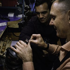 Master jeweller instructing apprentice jeweller in jewelry making.